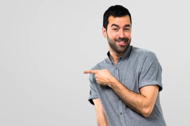 Handsome man pointing to the lateral on grey background