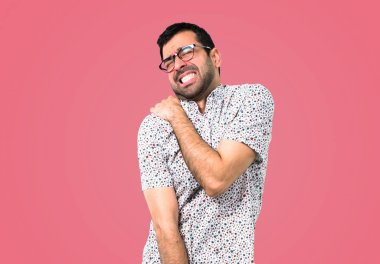 Handsome man with glasses with shoulder pain on pink background