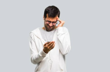 Man with glasses and listening music unhappy and frustrated with something. Negative facial expression on grey background