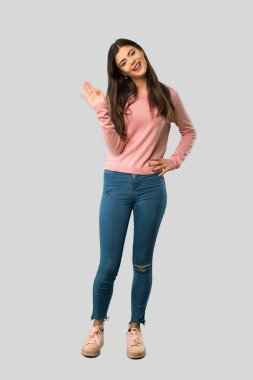 Full body of Teenager girl with pink shirt saluting with hand with happy expression on isolated grey background