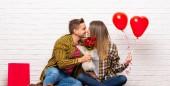 Pár v valentine den v interiéru s květinami a balónky s tvar srdce