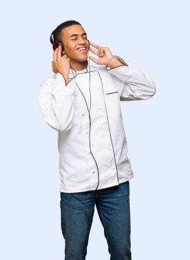 Young afro american chef man listening to music with headphones on isolated background