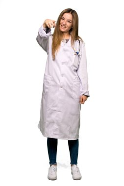 Full body Young doctor woman frustrated by a bad situation and pointing to the front on isolated background