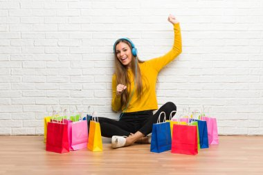 Young girl with lot of shopping bags listening to music with headphones and dancing