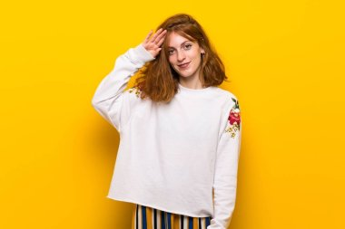 Young redhead woman over yellow wall saluting with hand