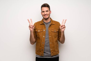 Handsome man over white wall smiling and showing victory sign with both hands