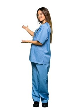 Full body of Young nurse pointing back and presenting a product