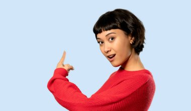 Short hair girl with red sweater pointing back on isolated blue background