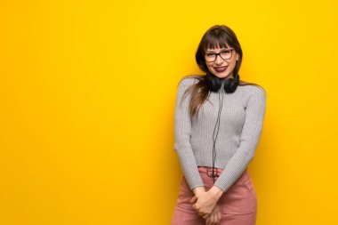 Woman with glasses over yellow wall with headphones
