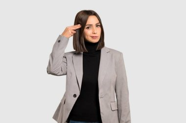 Young business woman with problems making suicide gesture on isolated grey background