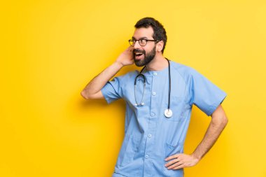 Surgeon doctor man listening to something by putting hand on the ear