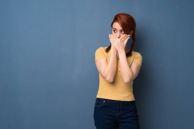 Young redhead woman over blue background covering mouth with hands