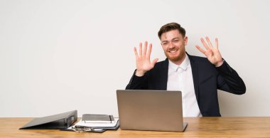 Businessman in a office counting nine with fingers