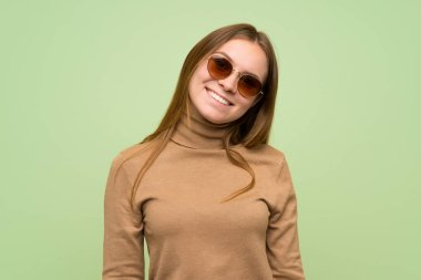 Young woman with turtleneck sweater with glasses and smiling