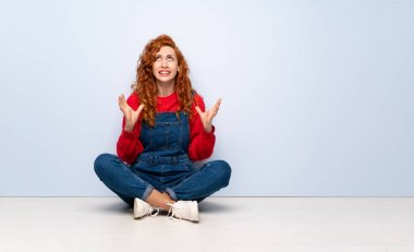 Redhead woman with overalls sitting on the floor frustrated by a bad situation