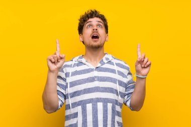 Blonde man over yellow wall surprised and pointing up
