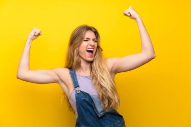 Young blonde woman with overalls over isolated yellow background celebrating a victory stock vector