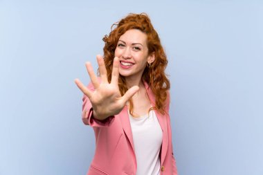 Redhead woman in suit over isolated blue wall counting five with fingers