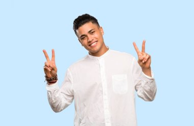 Young man showing victory sign with both hands on colorful background