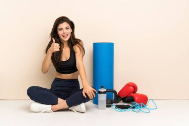 Teenager sport girl sitting on the floor with thumbs up because something good has happened