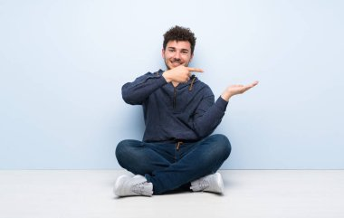 Young man sitting on the floor holding copyspace imaginary on the palm to insert an ad