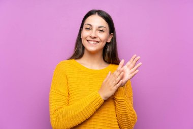 Young woman over isolated purple background applauding