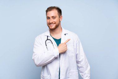 Handsome doctor man over blue wall pointing to the side to present a product