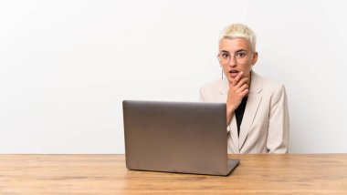 Teenager girl with short hair with a laptop surprised and shocked while looking right