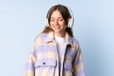 Young Lithuanian woman isolated on blue background listening music