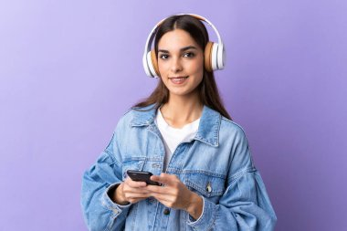 Young caucasian woman isolated on purple background listening music with a mobile and looking front