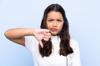 Young telemarketer Colombian woman over isolated blue background showing thumb down sign