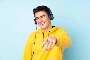 Teenager caucasian man isolated on purple background listening music