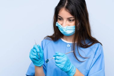 Woman dentist holding tools over isolated blue background