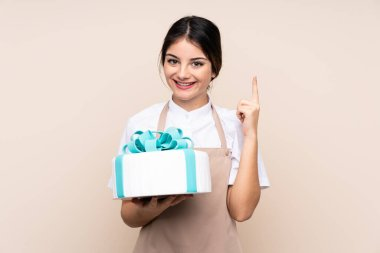 Pastry chef woman holding a big cake over isolated background pointing up a great idea