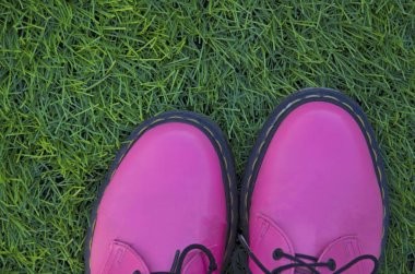 Creative pink shoes on green grass. Spring background
