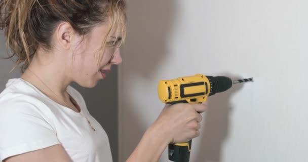 Bezár Portré fiatal nő dolgozik az építési területen, női lakás felújítás, egy lány fúróval fúrja a falat