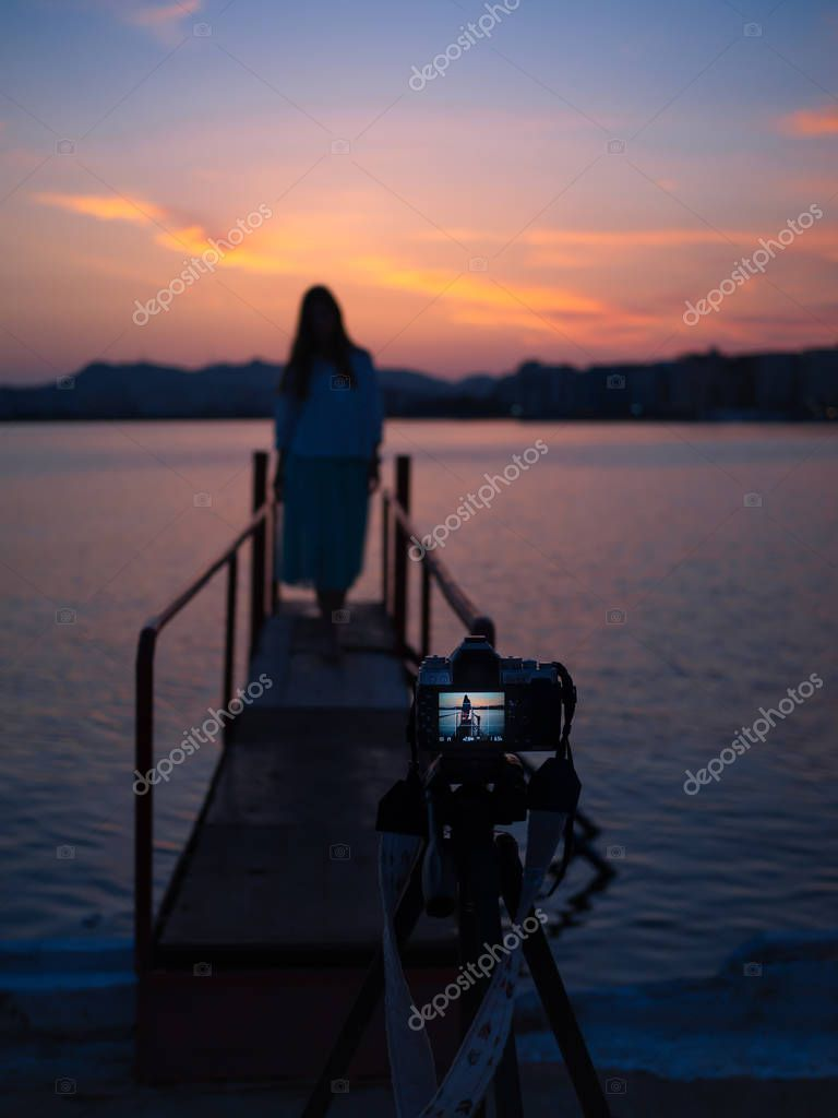 Photographer in motion. A beautiful sunset, young woman while shooting with beautiful blurred background.Blue and pink sky