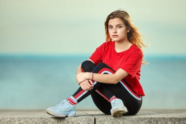 Teenage girl sits on sea shore.