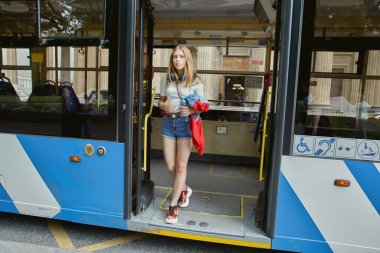 Woman is going out trolleybus on the public transport stop. Young blonde beautiful female in denim shorts is standing in the trolley bus doors.