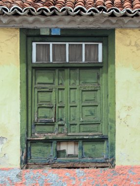 old traditional green painted window with closed shutters with p