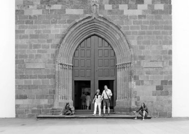 people outside the door of funchal cathedral in madeira with beggars sitting outside on the steps