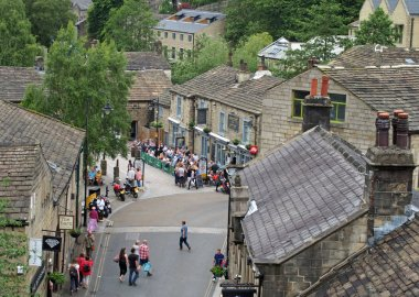 an aerial view of hebden bridge town center with people walking around shops and sitting outside a pub on a summer weekend