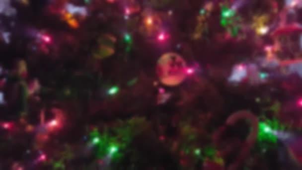 Vánoční strom s ozdobami a blikající světla zblízka s efekt rozostření