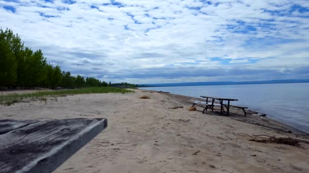 Picnic Table Along Beautiful Sand Beach Shore.  Daytime Sunny Vacation Shoreline Beach Destination in Summer With Beautiful Blue Sky.