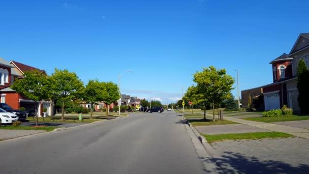 Sicht der Stadt Vorort Vier-Wege-Stoppschild Kreuzung Straße mit dem Verkehr am Tag. Fahrzeuge halten und fahren an Kreuzung mit Vollsperrung.
