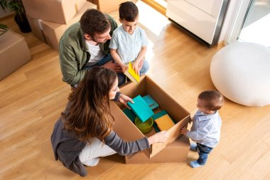 Young couple unpacking boxes with their two sons
