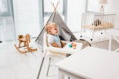 Photo happy toddler sitting in baby chair in nursery room with toy cubes
