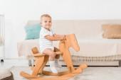 Fotografie rozkošný usmívající se batole sedí na hračku dřevěného koně