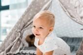 Fotografie s úsměvem roztomilé batole s baby vigvamu na pozadí