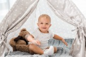 Photo smiling adorable toddler sitting in baby wigwam with fluffy teddy bear toy